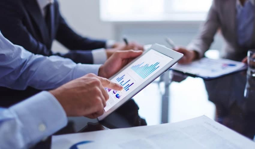 Office workers hands pointing to tablet showing graph on screen